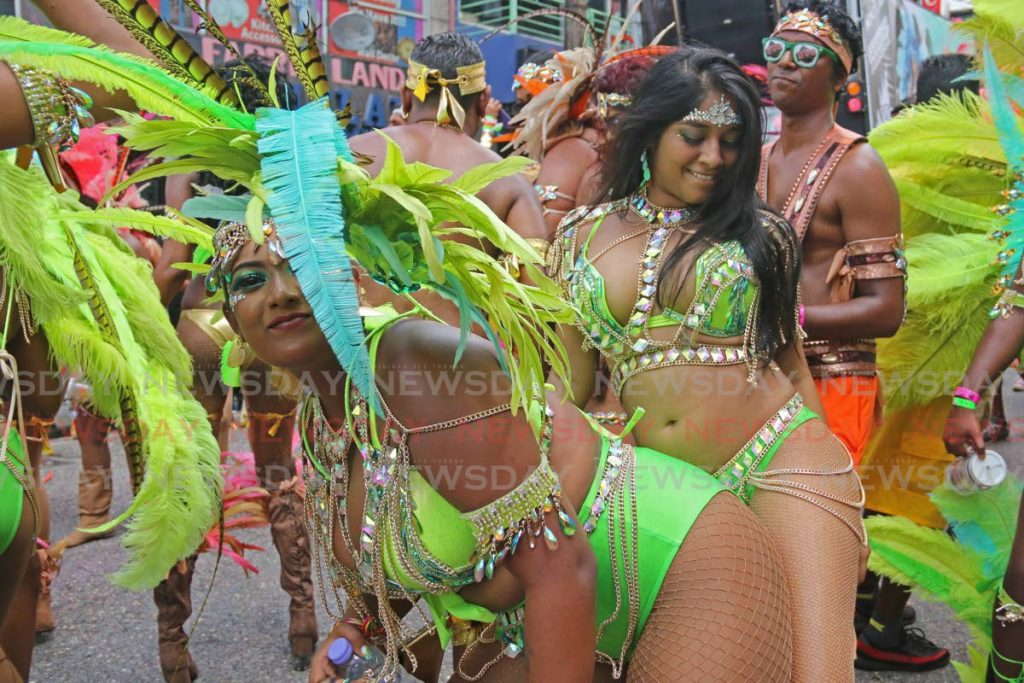 PRETTY MAS: These two masqueraders from the band Kalicharan enjoy themselves on High Street, San Fernando, on Carnival Tuesday. - Marvin Hamilton