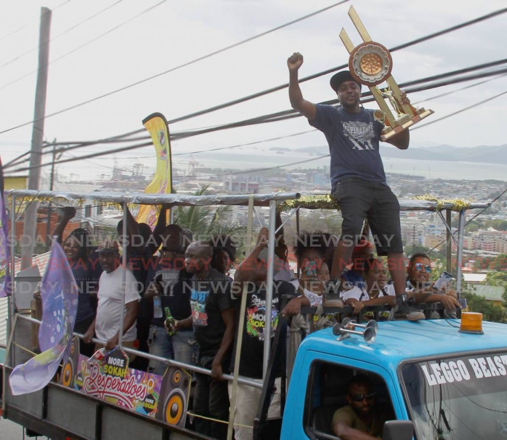 Adrian Glasglow, Captain of Desperadoes, proudly holds up the bands Panorama Large Bands victory trophy, on the lead truck of a motorcade at Victory Lap with the Champions of Panorama 2020 hosted by Desperadoes Steelband Orchestra, Laventille Road, Laventille - ROGER JACOB