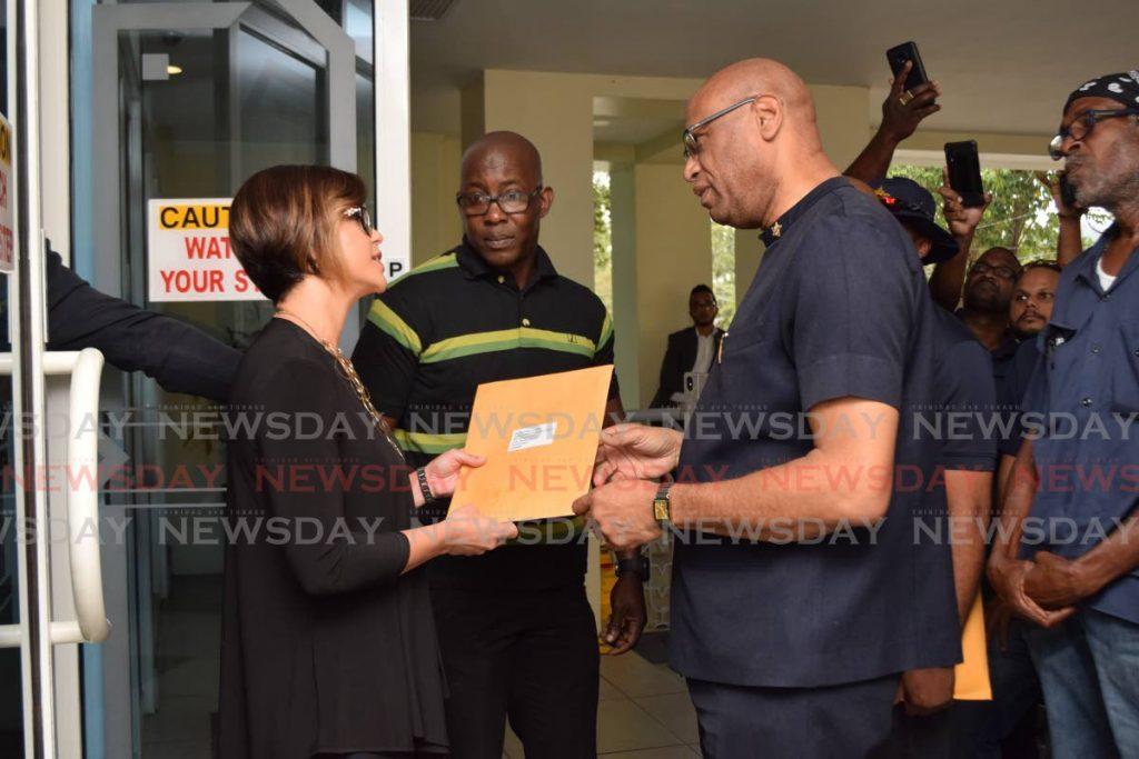OWTU president general Ancel Roget hands over a letter to BPTT vice president Giselle Thompson yesterday. - Vidya Thurab