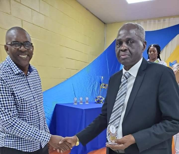 Former chief fire officer Roosevelt Bruce congratulates former deputy commissioner of police Glen Roach who was awarded for his contribution to the Chinapoo community in Morvant.  -