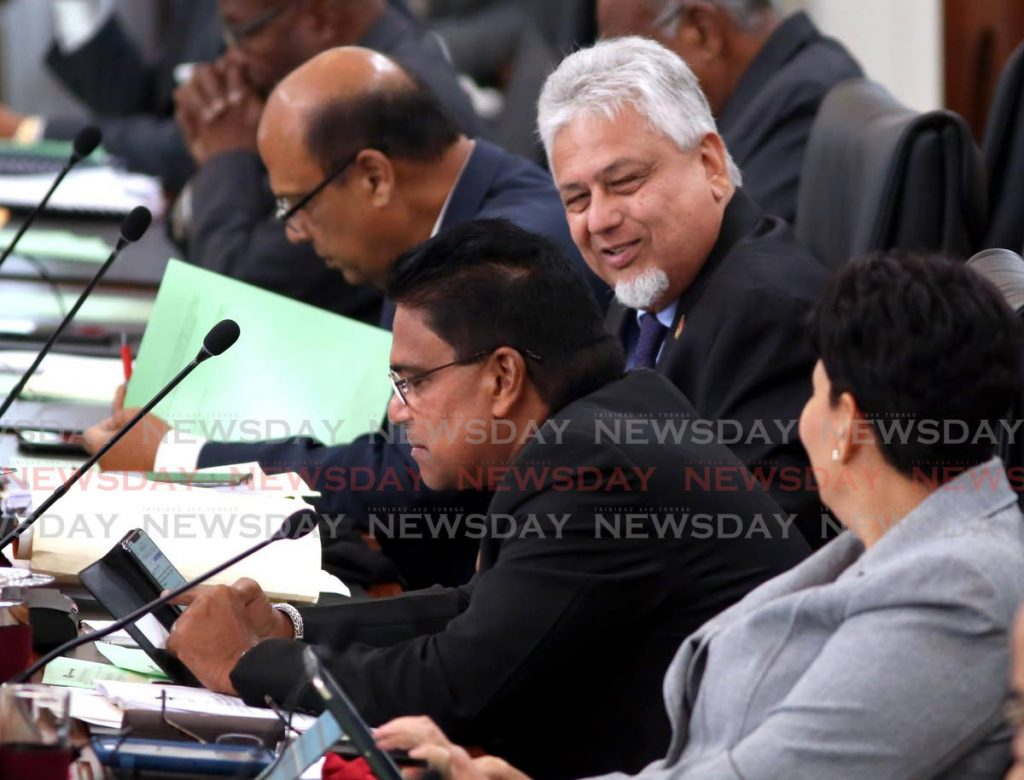 Oropouche East MP Dr Roodal Moonilal checks his phone in Parliament on Friday next to Opposition MPs Bhoe Tewarie and Christine Newallo-Hosein. - Sureash Cholai