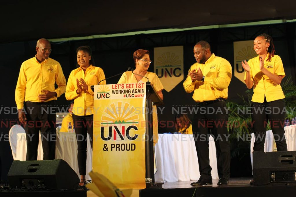 UNC political leader Kamla Persad-Bissessar, centre, presents, from left, Tarharqa Obika as the UNC candidate for Point Fortin, Michelle Benjamin for Moruga/Tableland, Sean Sobers as candidate for San Fernando West and Kenya Charles for St Anns East at the  UNC Monday night meeting held at the Union Claxton Bay Secondary School on Monday. - Lincoln Holder
