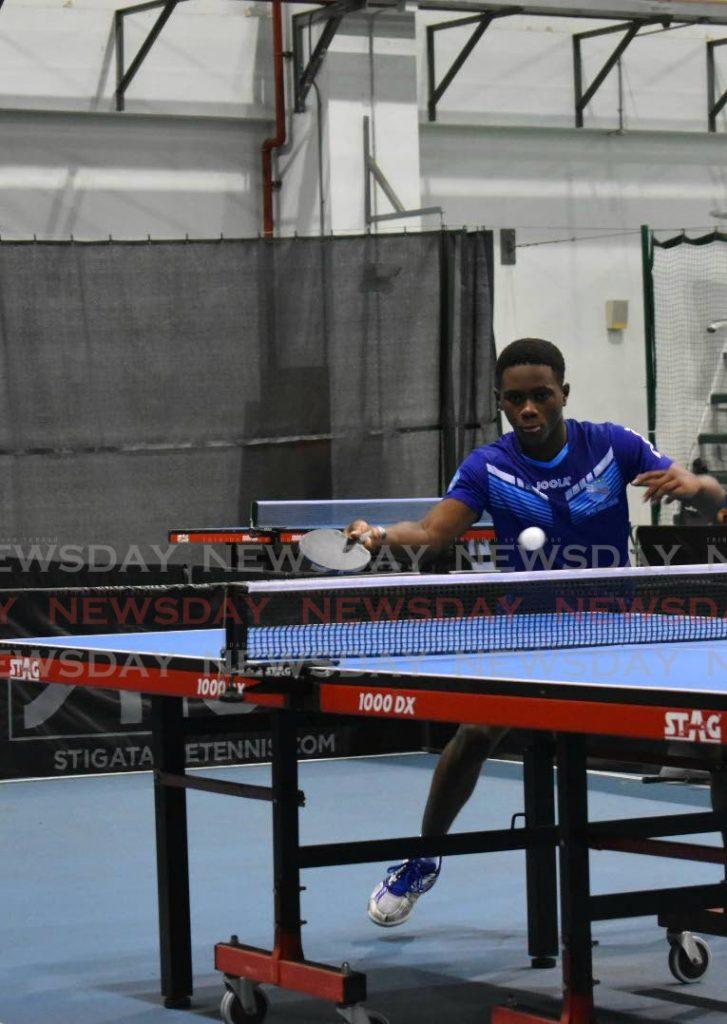 Derron Douglas returns a serve during the ICWI Junior Super Singles tournament. - Sherdon Pierre