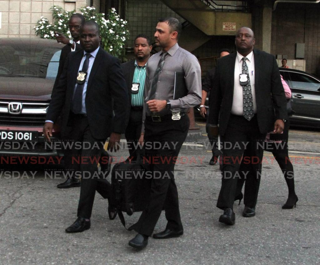 Police officers leave Express House on Independence Square, Port of Spain after conducting a search. - Ayanna Kinsale