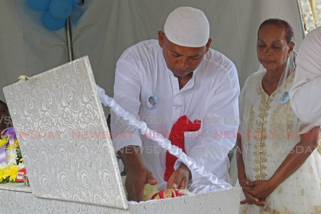 Sheriff Mohammed and Sheriffa Shyam, parents of Shazard Mohammed, say farewell to their son at his funeral at Platanite Trace, Rochard Road, Penal. - Marvin Hamilton