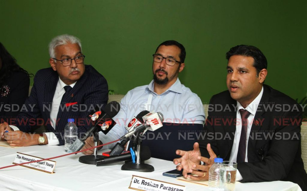 Ministry of Health Chief Medical Officer Dr Roshan Parasram, right, speaks at a press conference at the Ministry of Health, Port of Spain on Thursday, as Minister of Health Terrence Deyalsingh, left, and Minister of National Security Stuart Young look on. - Ayanna Kinsale