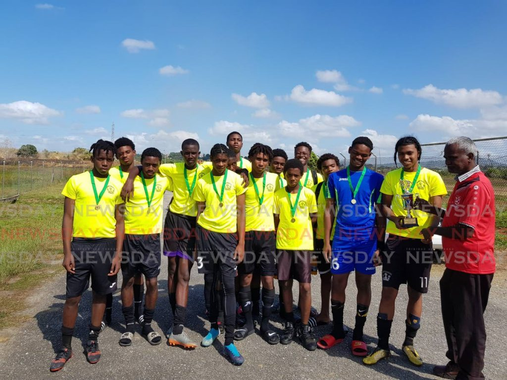Under-18 Champions Crown Trace FC receive their trophy and medals from Oragisining Committee member Ramnarace Samuel (right) -