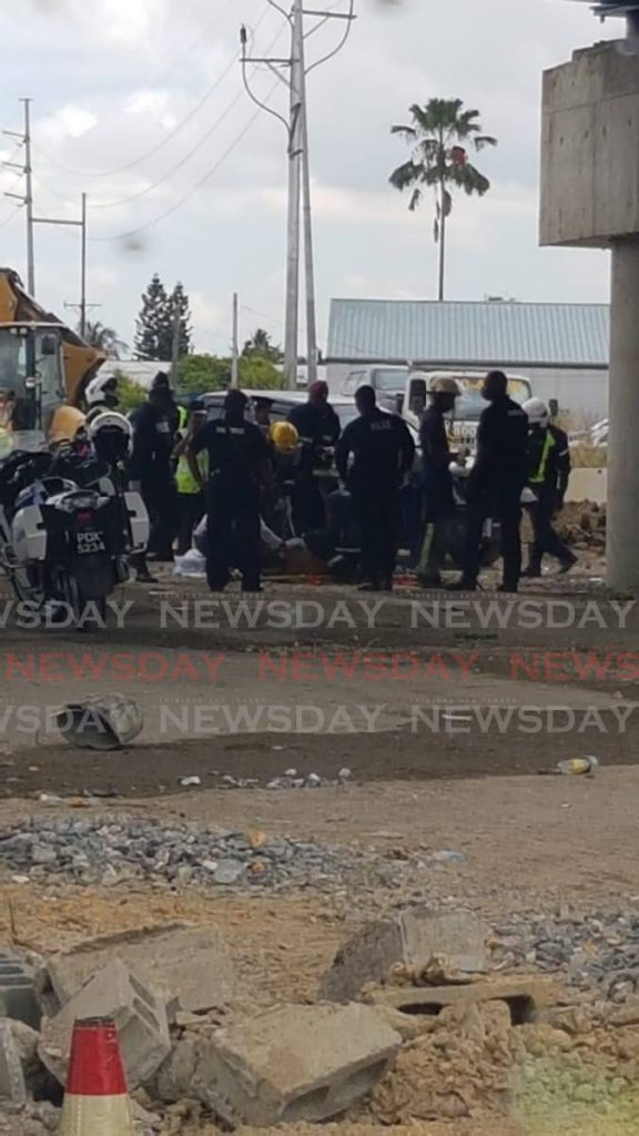 In this image shared on social media police and fire officers attend to the man who was injured after he fell from the Curepe interchange on Saturday. -