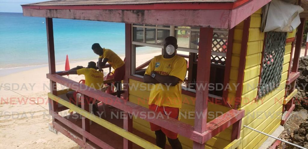 Lifeguard Neil Potts wears a dust mask while on duty on Monday at Store Bay. - KINNESHA GEORGE-HARRY