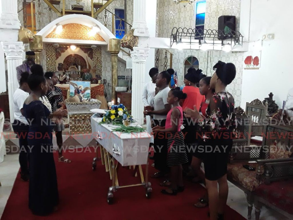 Relatives and friends of Sadiuq Maloney, 17, surround his coffin to pray at his funeral in Chaguanas on Monday.   PHOTO BY ELIZABETH GONZALES -