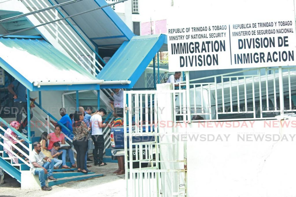 Persons gather outside of the Immigration Division in San Fernando which has adjusted its operations in response to covid19. - CHEQUANA WHEELER
