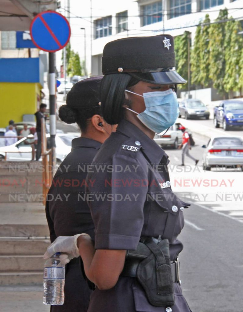 In this file photo, a policewoman wears gloves and a mask as she works on traffic duty in San Fernando. - Vashti Singh