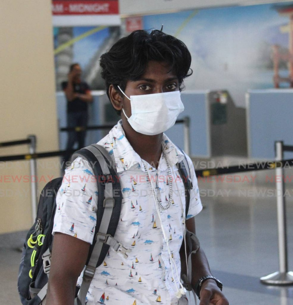 A passenger wears a mast at Piarco International Airport on Wednesday. Government on Saturday announced that all borders will be closed from midnight on Sunday. - Angelo Marcelle