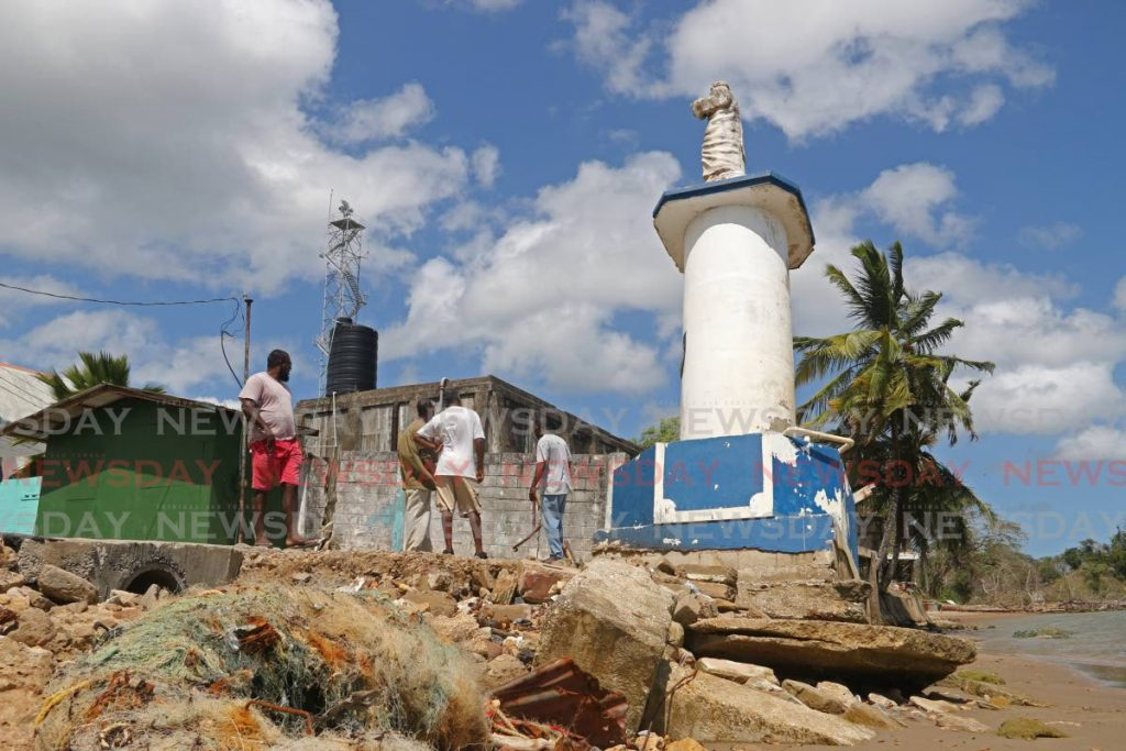 Villagers look at the leaning statue of St Peter at Moruga Road, Grand Chemin. - Marvin Hamilton