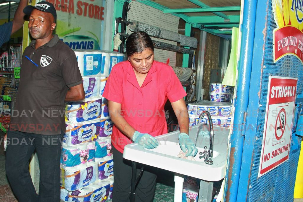 Debra Choutee who works at Harris Mega Store, Mucurapo Street, San Fernando cleans a sink which the store provided for customers' use before they enter the grocery. - CHEQUANA WHEELER