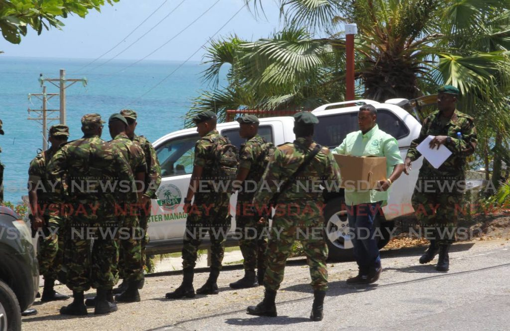 Soldiers deliver food to the 68 quarantined people at the Seventh-Day Adventist Church camp at Balandra in Toco on Thursday.  PHOTO BY ROGER JACOB - ROGER JACOB