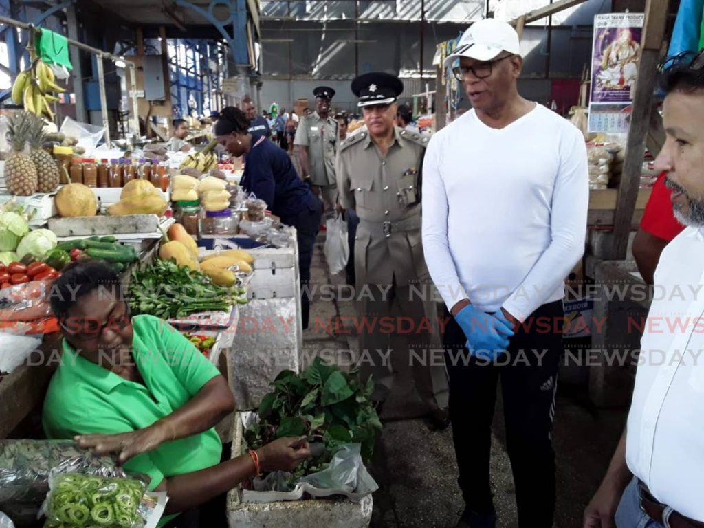 San Fernando mayor Junia Regrello listens to a vendor during a visit to the central market in San Fernando on Sunday morning.  PHOTO BY VASHTI SINGH - VASHTI SINGH