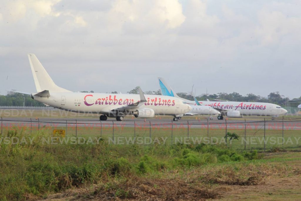 Caribbean Airline planes parked at the Piarco International Airport on March 22. The covid19 pandemic has caused global travel and tourism to grind to a virtual halt. - ROGER JACOB