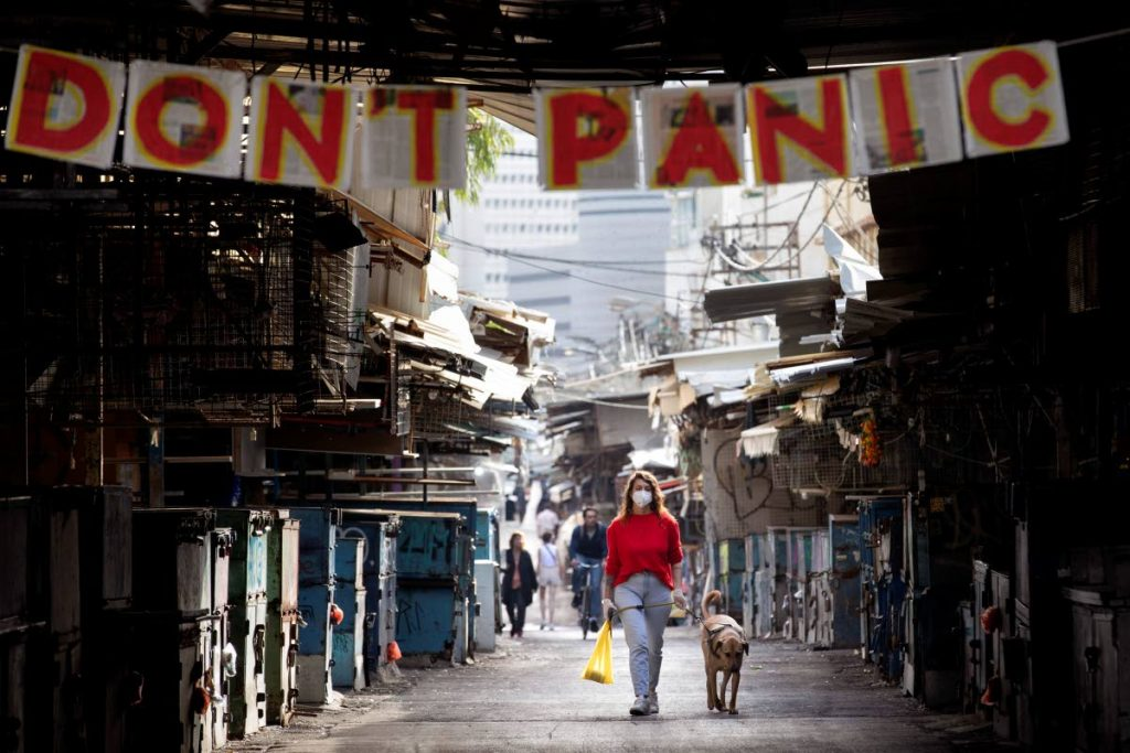 "A woman walks her dog under a ""don't panic"" sign hanging on the entrance of a food market that was shut down in Tel Aviv, Israel,  - AP Photo"