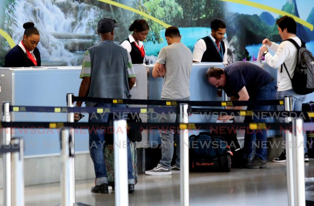 Passengers line up at the British Airways counter at Piarco International airport to catch the first of three repatriation flights to the UK on Monday. - SUREASH CHOLAI