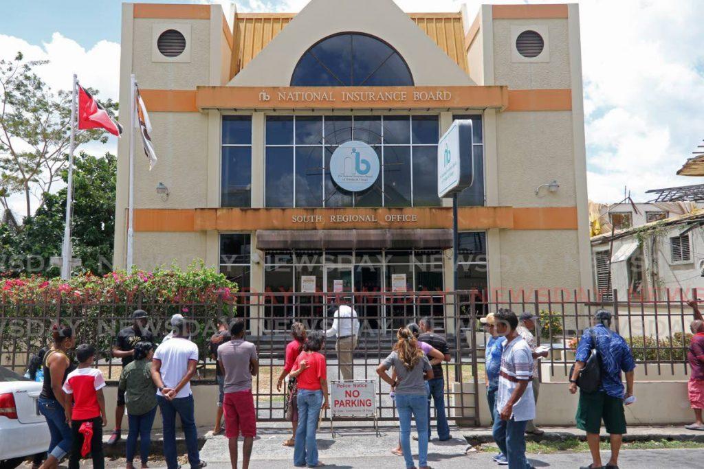 People gather outside the National Insurance Board, South Reginal office on Harris Promenade, San Fernando on Tuesday. - Marvin Hamilton
