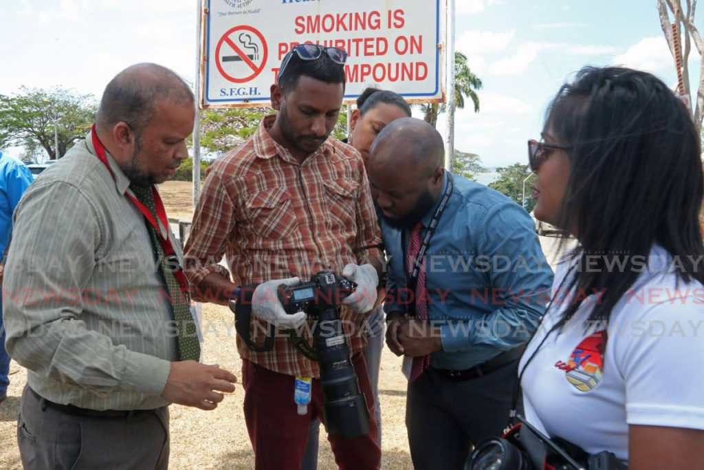 Express photographer, Dexter Phillip shows officials of the San Fernando General Hospital photos captured of security officers in a clash with media workers on Wednesday afternoon at the hospital's carpark. - Marvin Hamilton