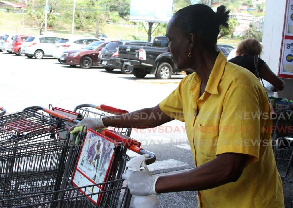 Marlyn Williams sanitises a trolly in an attempt to prevent the spread of the coronavirus at Massy Stores, Westmoorings.  - Ayanna Kinsale