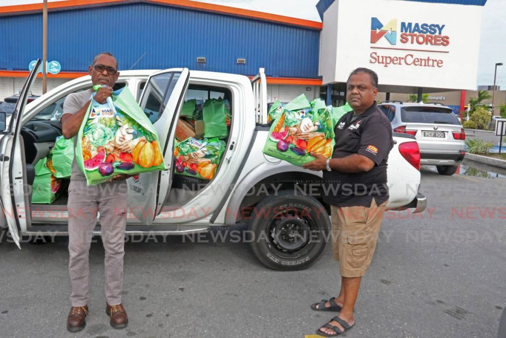 Dillon Boodoosingh, left, with divisional manager Fuel and Transport Mahendra Seenath of Rahamut's Enterprises Ltd loading up the company's vehicle with Massy's Bargain Bags for Rahamut's Enterprises daily paid employees at Massy Stores, La Romain. - Marvin Hamilton