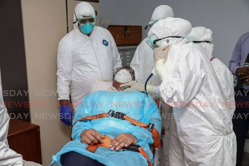 In this February 7 file photo, doctors simulate the protocols in place for examine someone for the coronavirus for quarantine at Caura Hospital. THe exercise was done at Piarco International Airport. - JEFF K MAYERS