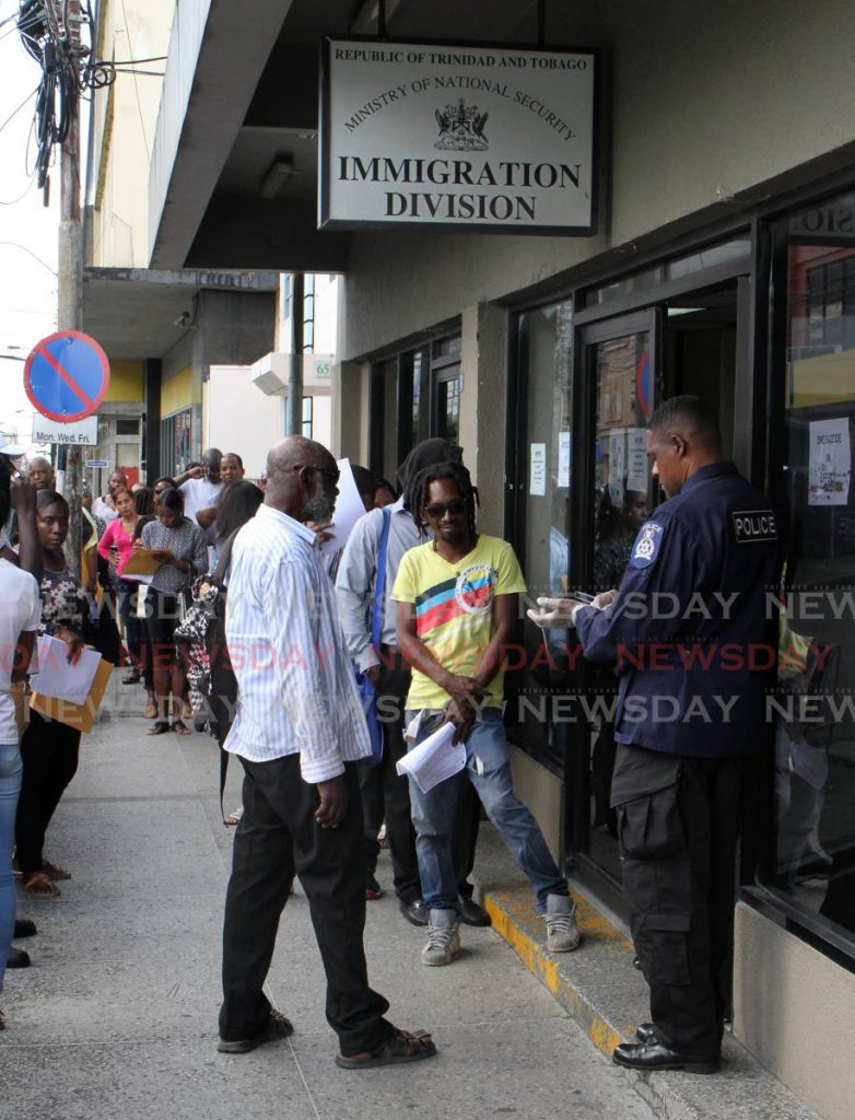 File photo - People wait outside the Immigration Division office on Frederick Street, Port of Spain. -