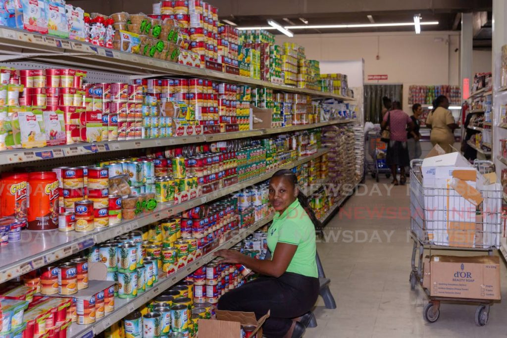 FULLY STOCKED: An employee at Penny Savers, Bon Accord, Tobago packs goods on shelves last month. - DAVID REID