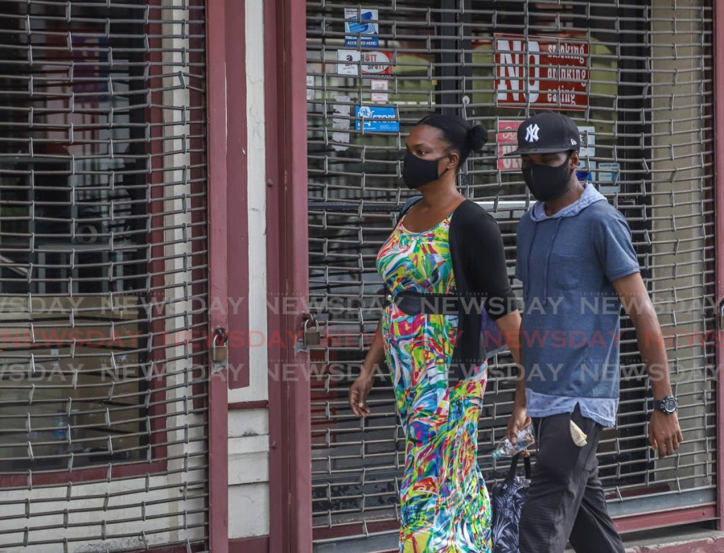 A couple wearing masks walk along Queen Street, Port of Spain on March 27. The CMO says people can wear cloth or homemade masks to free up surgical or N95 for medical practitioners. - JEFF K MAYERS