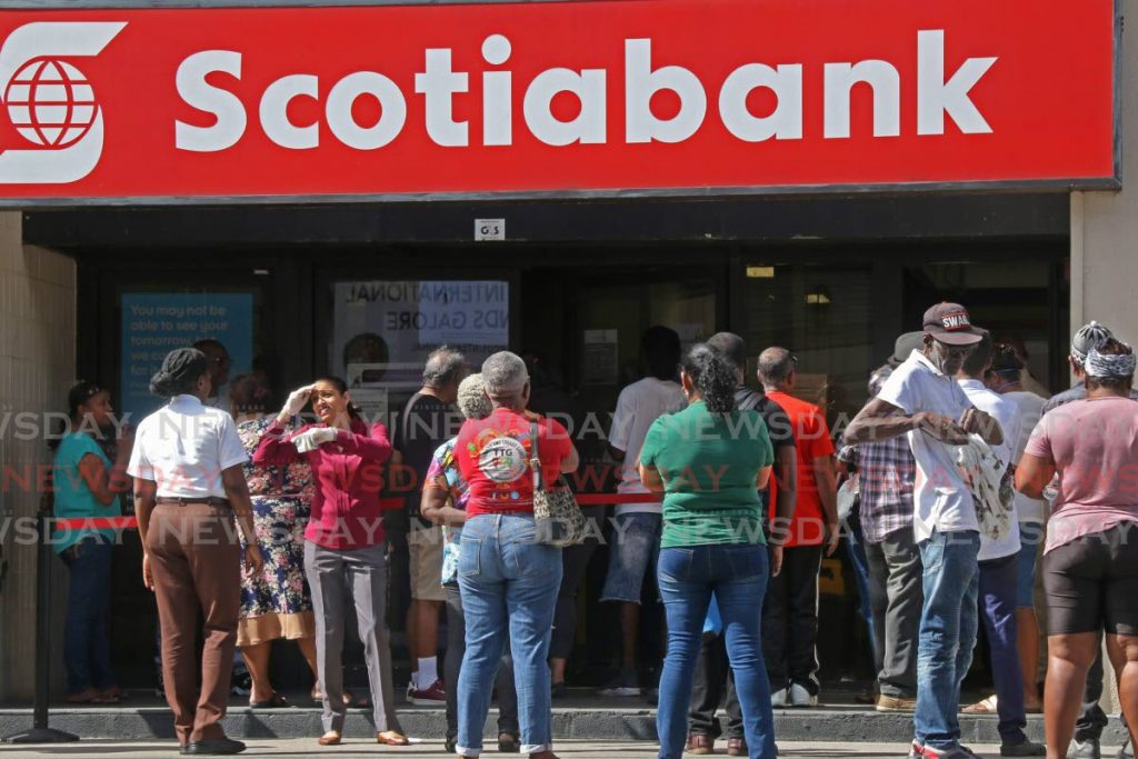 Staff of Scotiabank, High Street, San Fernando assisted and advised customers as they encourage them to practice social distancing while waiting. Photo: Marvin Hamilton