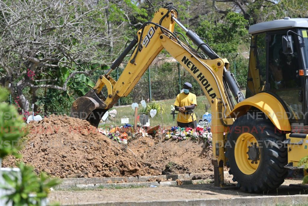 BURIED: A backhoe is used to bury Tobago's first covid19 fatality on Sunday at the Buccoo public cemetery. PHOTO BY LEEANDRO NORAY -