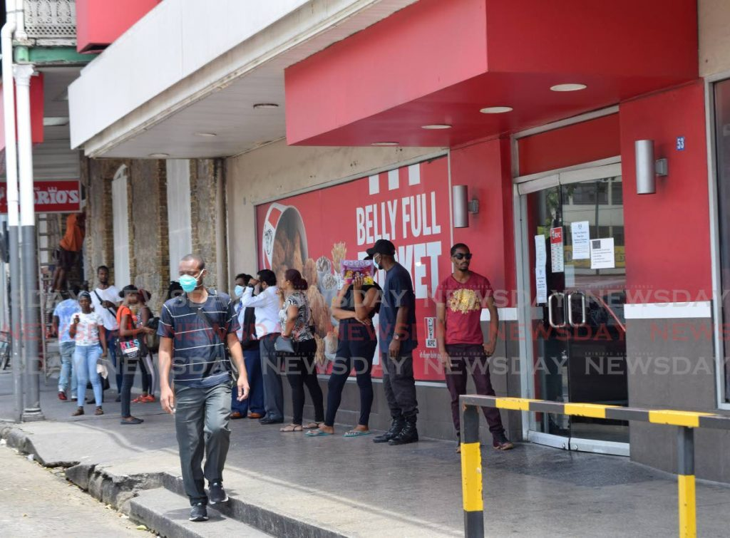 A man wearing a mask walks past customers waiting in line outside KFC Independence Square, Port of Spain,  to get last minute deals after Government ordered all restaurants to close.