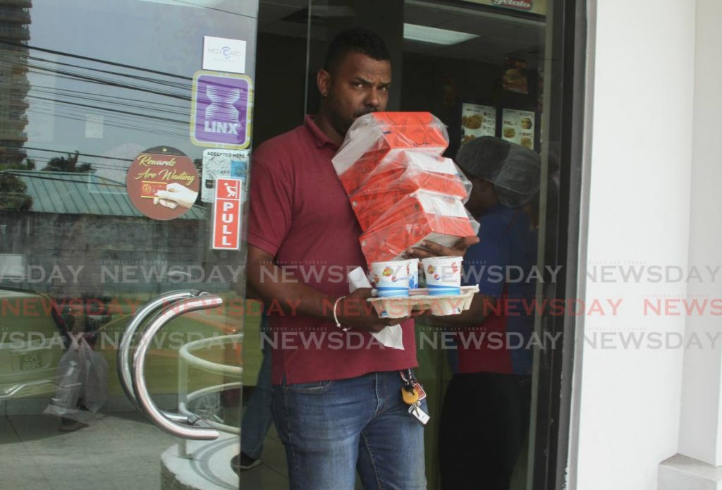 A customer leaves Churches Chicken, Glenco with his order - Ayanna Kinsale