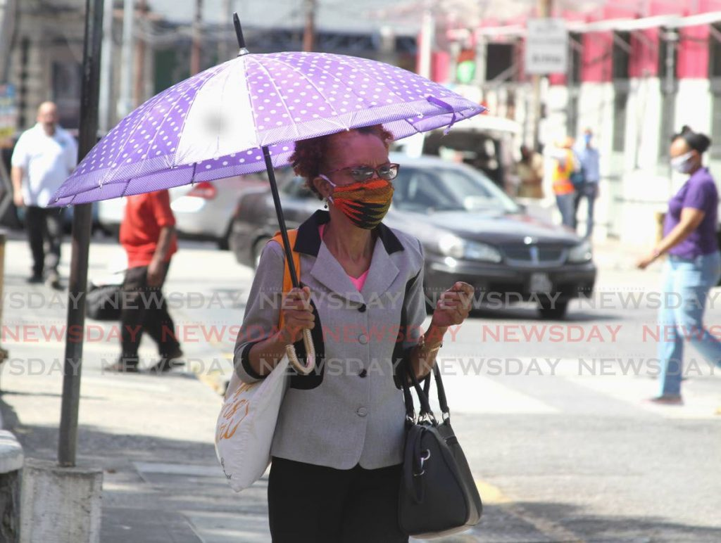 A woman walks through the capital city Port of Spain wearing a face mask on Tuesday April 14 2020. - Ayanna Kinsale