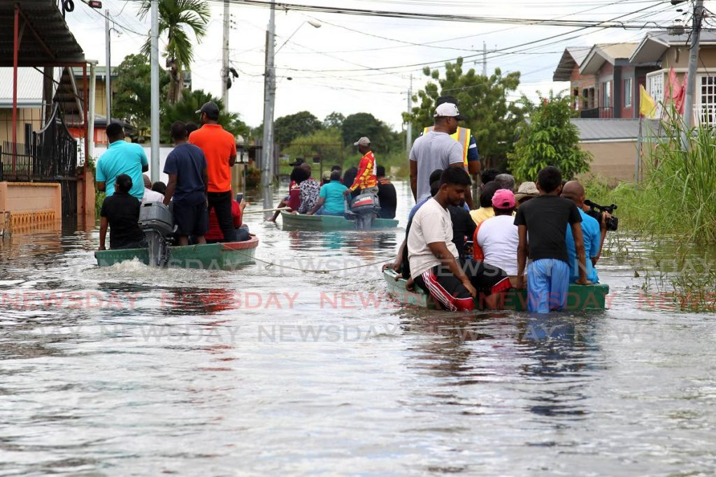 In this 2018 file photo, residents of El Socorro South, use boats to come to the aid of neighbours inundated by flood waters after heavy rainfall. As the rainy and hurricane seasons approach, consideration must be given to the nature of possible relief efforts as the country continues to battle the covid19 pandemic. -