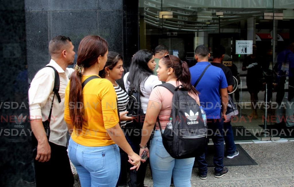 FILE: Venezuelan nationals line up outside the Ministry of National Security last year  to collect registration cards which allows them to work and live in this country for up to one year. - SUREASH CHOLAI