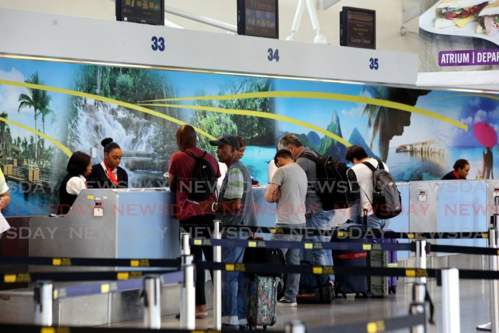 Flashback: Passengers at the British Airways counter at the Piarco Airport checking in for one of three repatriation flights to the UK in March. - SUREASH CHOLAI