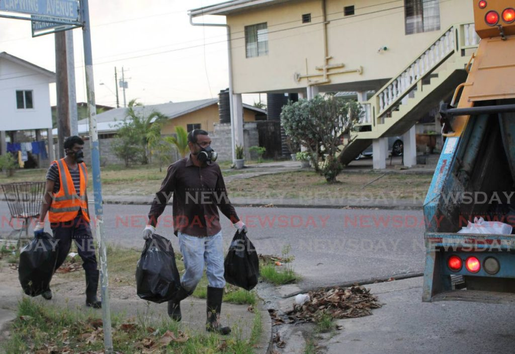A sweat-drenched Marcelle, right,  gathers bags of garbage from a nearby street.  - Fabian Birch