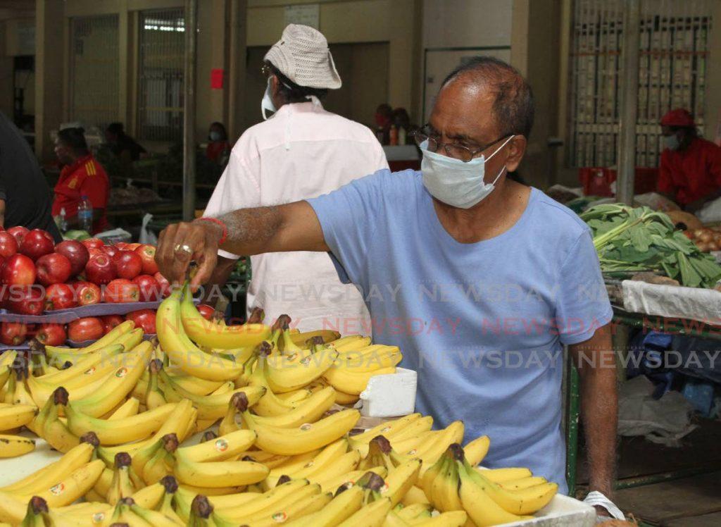 A customer in the Tunapuna market choosed some bananas.  - Ayanna Kisnale