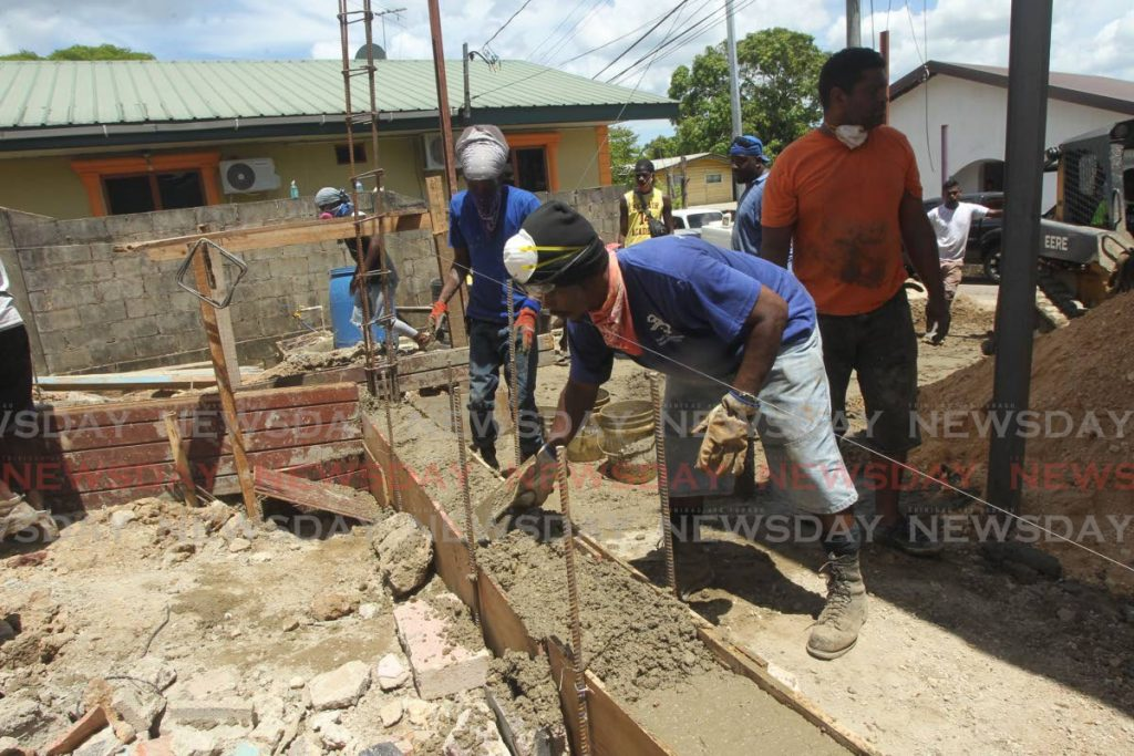 FILE PHOTO: Volunteers work to rebuild a house that was destroyed by fire in Claxton Bay last month. Government has allowed the construction and manufacturing sectors to be fully reopened today. -