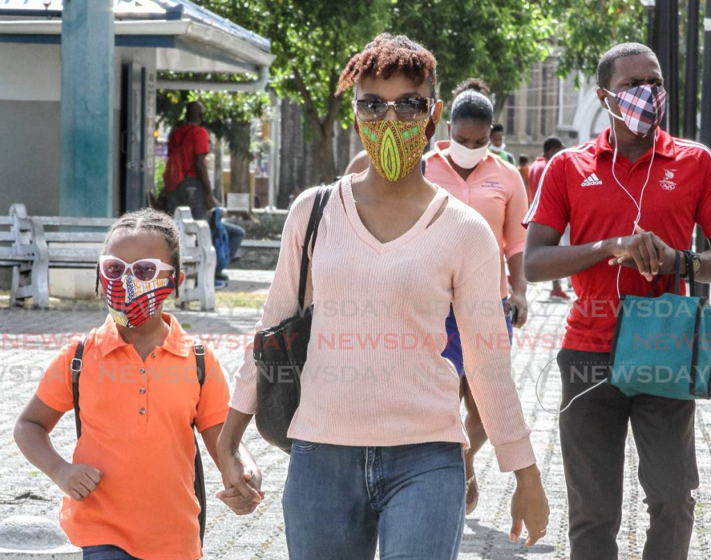 People walk on the Brian Lara Promenade in Port of Spain with cloth face masks.  - ANGELO MARCELLE