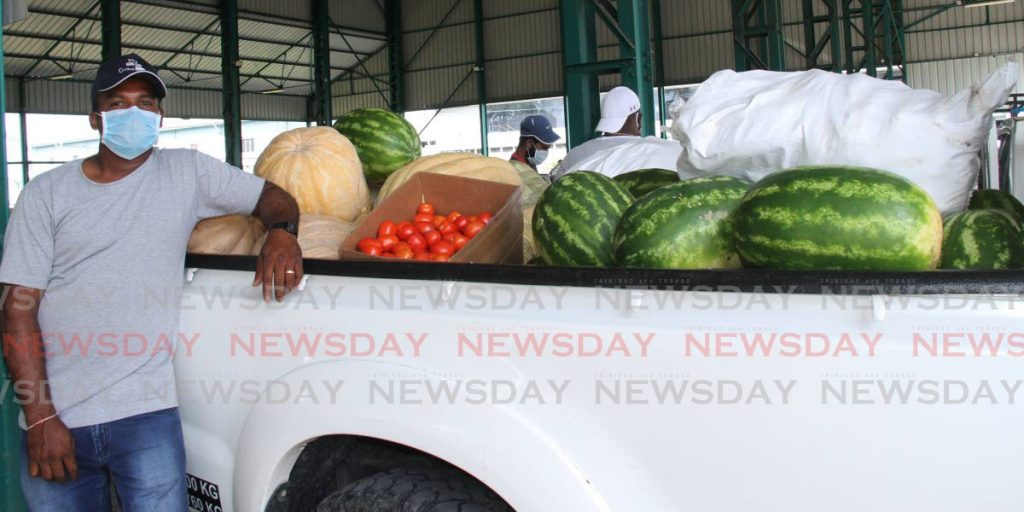 Ricky Ramdhan stands near his produce at the Namdevco farmers' market in Chaguanas.  - Vashti Singh