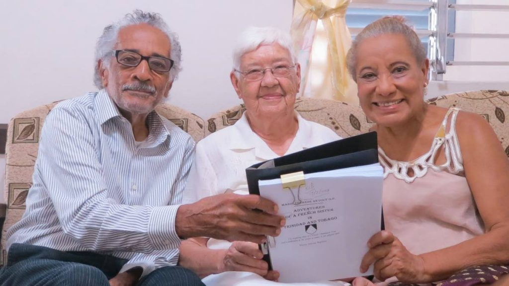 From left, Owen Baptiste, Sister Marie Thérèse Rétout and Rhona Baptiste looking at the manuscript of the biography in 2018. - Delia Mendez