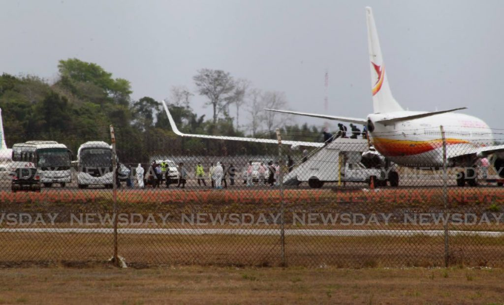 Sixty nine nationals disembark a Suriname Airways flight at Piarco on Friday and were immediately taken to Debe where they would be kept in isolation. - ROGER JACOB