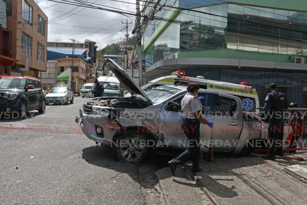 Police, fire officers and an ambulance at the scene of an accident in which two women were knocked down by a pickup truck on Penitence Street, San Fernando, on Monday. - Marvin Hamilton
