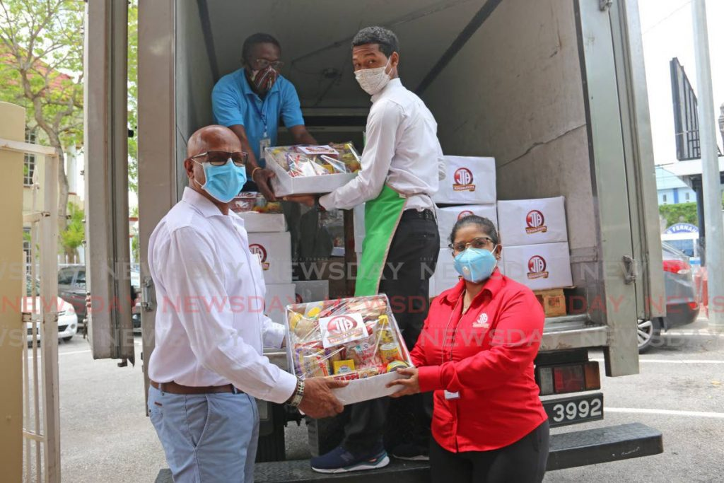 JTA staff offload hampers from a truck as San Fernando Mayor Junia Regrello recieves hampers from sales and marketing manager Marisa Mc Clashie for people who would have been affected with job loss owing to covid19. - Marvin Hamilton