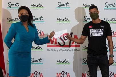 Minister of Sport and Youth Affairs, left, presents a cheque to boxer Michael Alexander, at the ministry's office on April 27. - Photo courtesy the MSYA